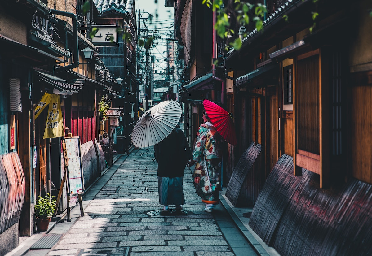 Figures shot from behind walking down street in Kyoto holding Japanese parasols
