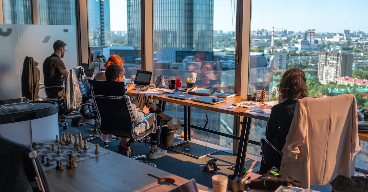 students looking out of office window at a city scape during summer internship