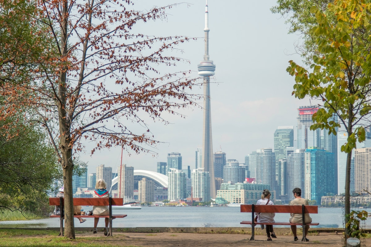 view of Toronto with trees in foreground and international students on benches