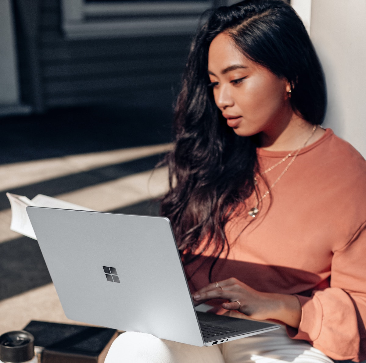 student filling in UCAS application on laptop outdoors