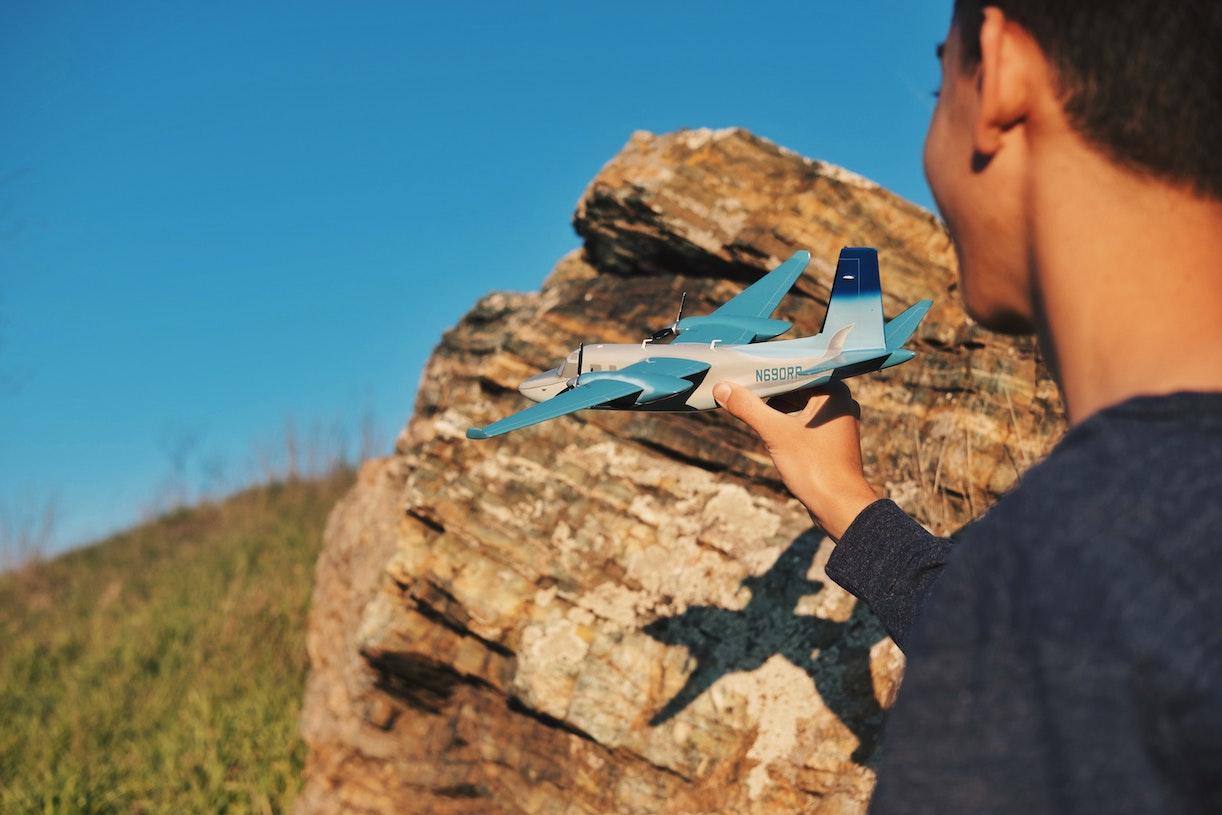 student from the class of 2022 about to launch a model aeroplane into a blue sky