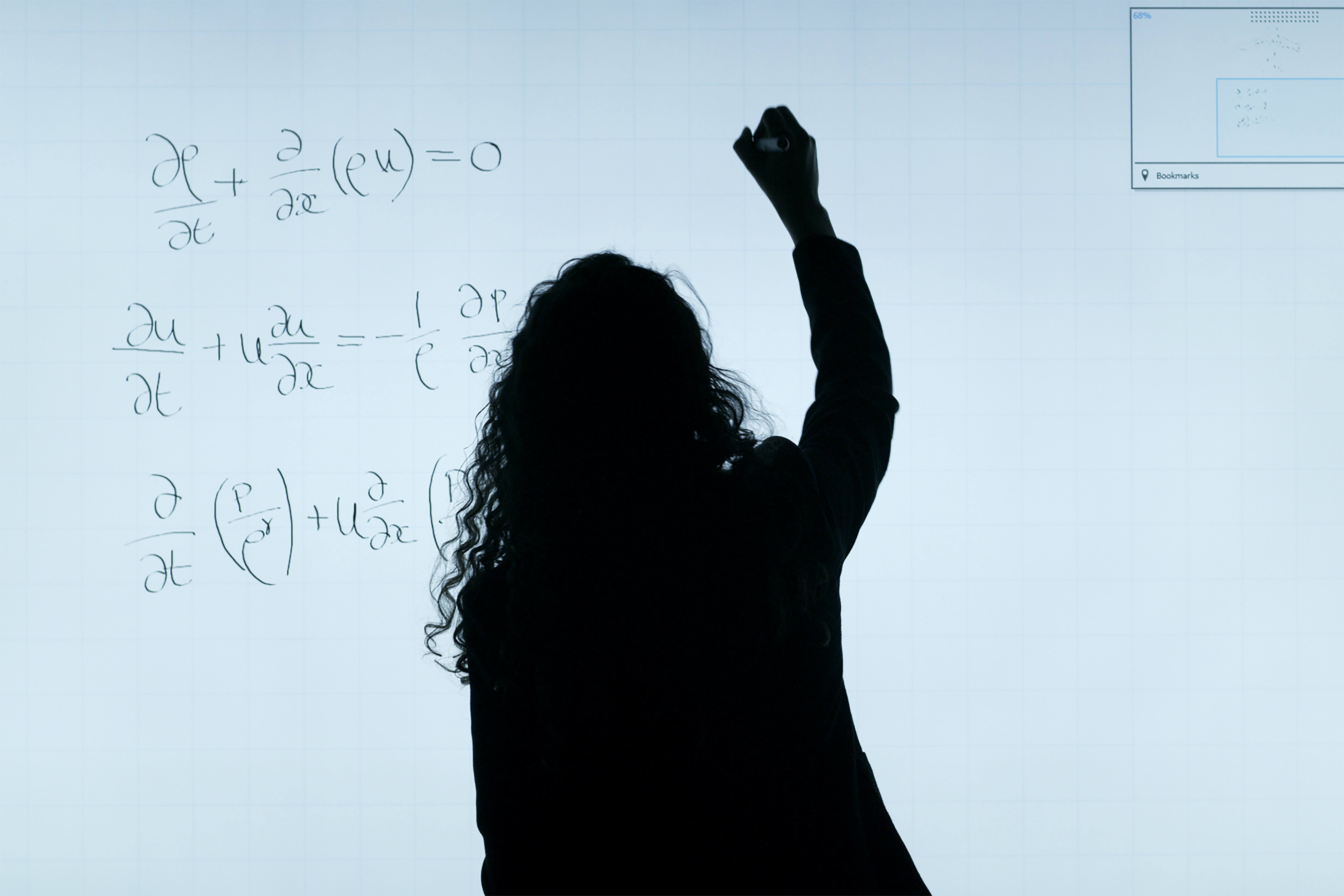 silhouette of student writing maths equations on white board