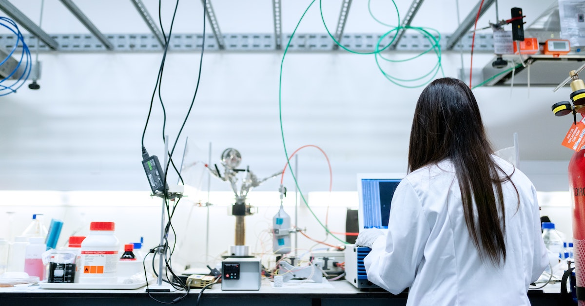 Student who chose a scientific degree major shot from behind in lab coat with cables